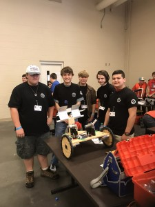 Titan Robotic team members standing around their robot on a table