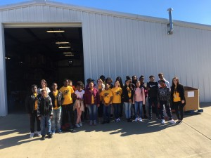 Group of Litchfield Middle School students in front of a large warehouse