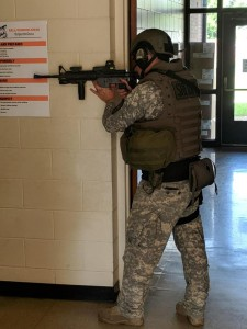 Camouflaged armed first responder in a hallway poised with a rifle